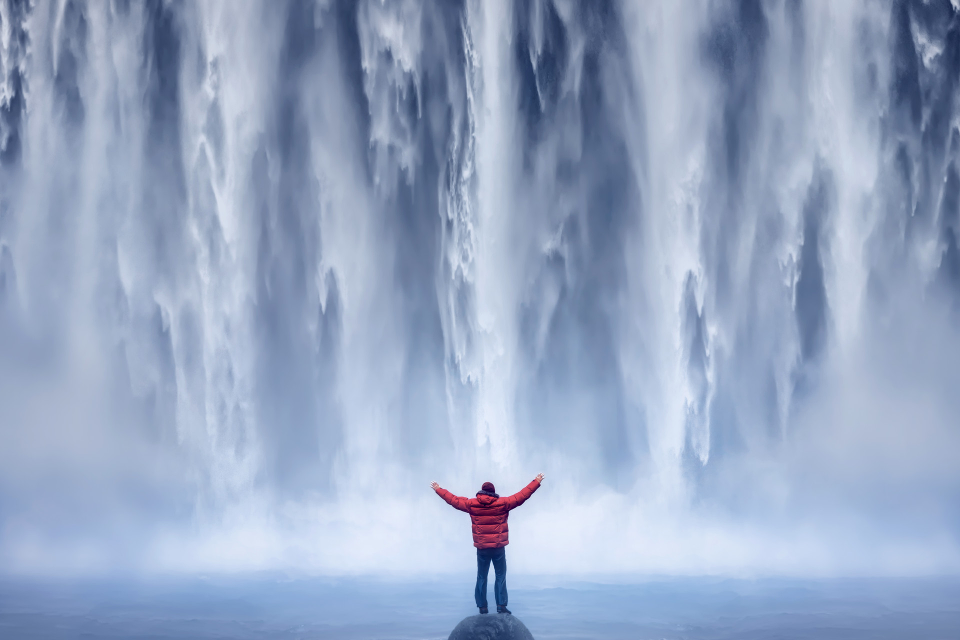 Man with Red Jacket in front of Waterfall